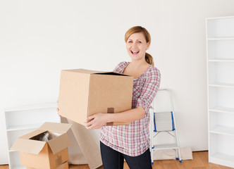 Smiling woman carrying cardboard boxes