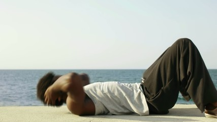 african man exercising abs near the sea
