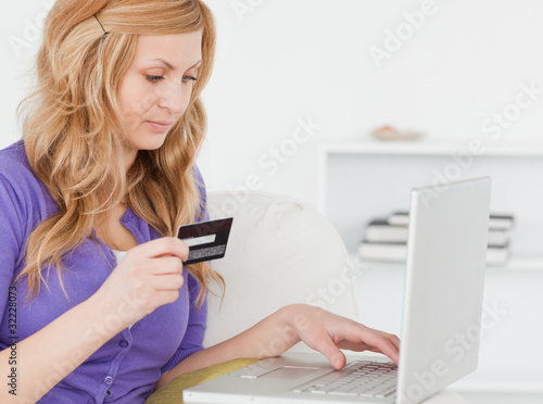 Concentrated woman sitting on a sofa is going to make a payment