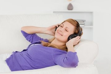 Good looking red-haired woman listening to music and enjoying th