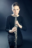 Young musician woman playing oboe musical instrument