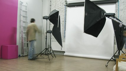 Photographer and kid adjust equipment at photo studio