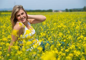 portrait d'une femme souriante dans un champs de colza
