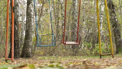 Two swings colored in different colour swaying in park