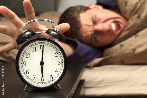 Alarm clock with male model in bed in background.