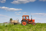 An old red tractor spraying crops with pesticide