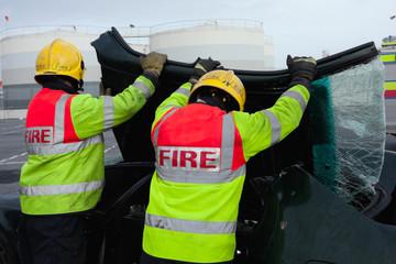 Firemen removing brocken windscreen at car crash