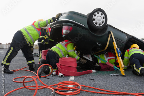 Firemen with equipment at car crash