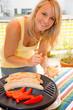 Junge Frau beim Grillen
