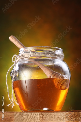 Pot of honey and wooden stick in it