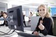 Mitarbeiterin im Callcenter lächelt freundlich mit Daumen hoch