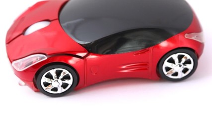 computer mouse in form of sport car, rotating on white