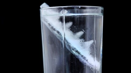 close-up shot of glass with water and ice rotating on black