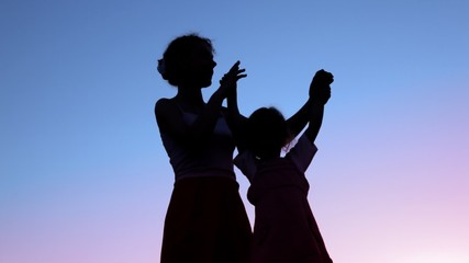 mother holding hands of little daughter against sunset sky
