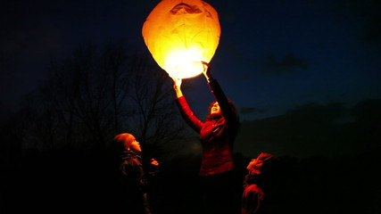woman holds chinese lantern, children look, then she releases