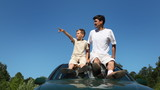 father and son sitting on roof of car and talking, part2