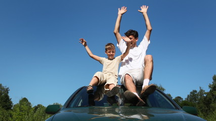 father, son sitting on roof of car, they waved with hands, part2