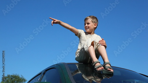 boy sitting on roof of car, pointing to something by hand