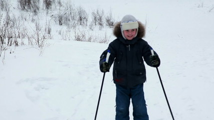 boy moves down on skis coming nearer to chamber in winter