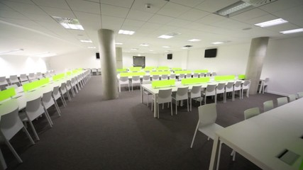 Light room without windows, white elongated tables and chairs.