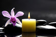 aromatherapy candle and pink orchid on zen stones