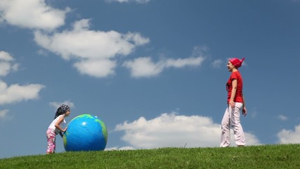 mother and daughter rolling inflatable ball to each other