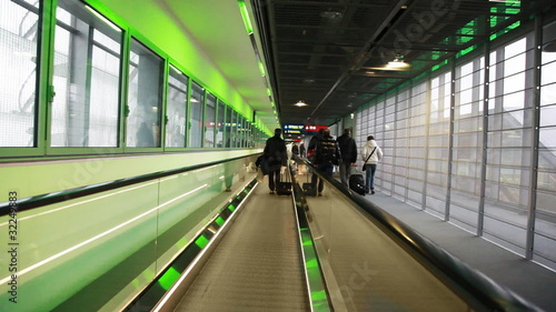 people go to corridor moving escalator at exit from airport