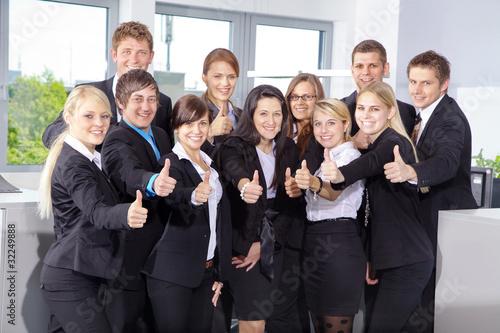 Motivierte Mitarbeiter halten lächelnd Daumen hoch