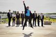 Junger Mitarbeiter springt jubelnd vor Freude und Erfolg, Team