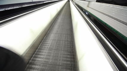 horizontal escalator and feet of people walking on it in airport