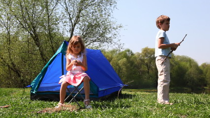boy and girl plays near blue tent at forest in summer day