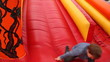 boy drives off with big red inflatable rubber slides