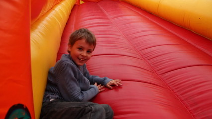 boy drives off sitting  with inflatable rubber slides