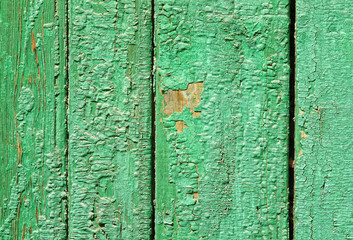Closeup of wooden boards with green peeling paint texture