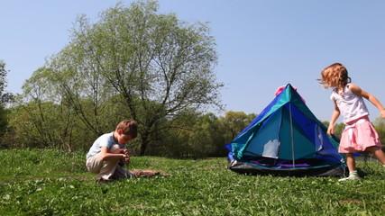 boy tries to take flame by primitive way, girl near tent