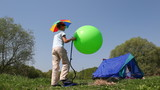 Boy pumps ball, girl inside tent makes order at forest