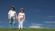 mature couple stands on grass against sky