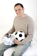 Young father smiling to camera - with baby clothes