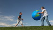 senior with grandson throw inflatable Earth against sky