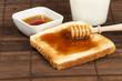 toast mit honig, milch und einem honiglöffel