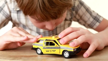 The boy playing with yellow toy taxi car on wooden table
