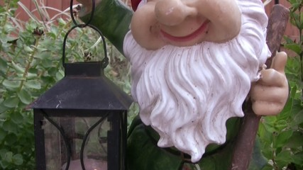 Sculpture of dwarf with lamp in hands in garden.