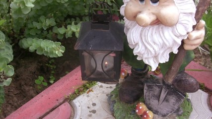 Approach of lamp with a candle in hands of the garden dwarf.