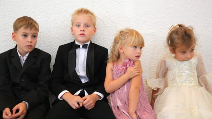 Four children in celebratory clothes sit in room