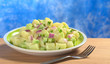 Potato salad with green and red onions and cucumber