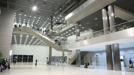 business center with visitors, escalators move between them.