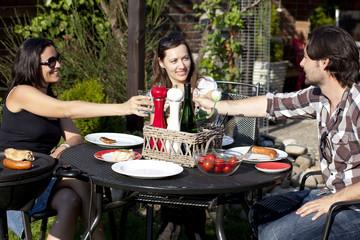 Drei Personen stossen an bei Gartenparty