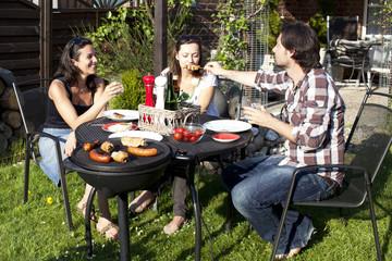 Drei Personen bei Gartenparty mit Grillen