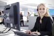 Mitarbeiterin im Callcenter mit Head Set telefoniert freundlich