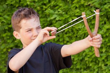 Kind - Junge schießt einen Stein mit der Steinschleuder